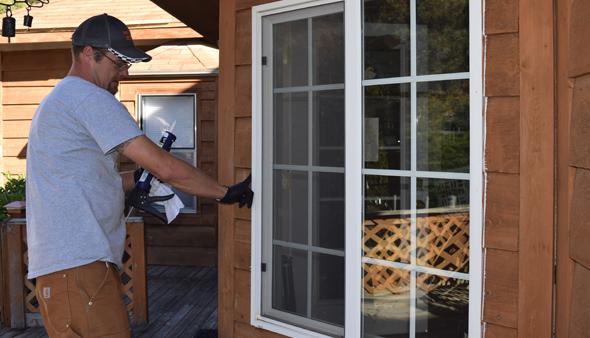 Community Action crew caulks window