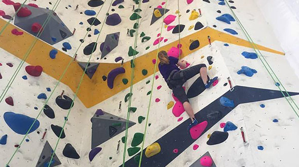 Photo of young woman climbing colorful wall in Riverfront Rock Gym