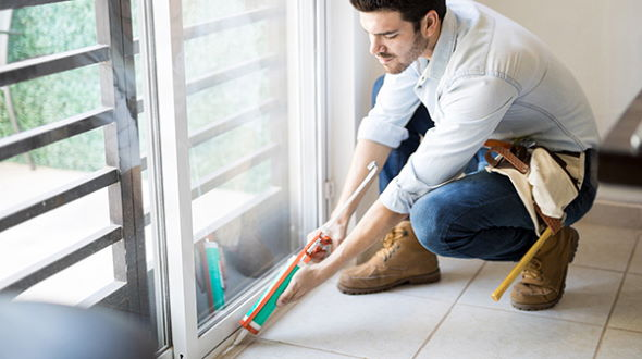 Person uses caulking gun to seal around sliding glass door