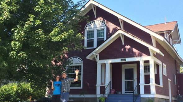 Mark and Thea wave in front of their energy efficient historic home