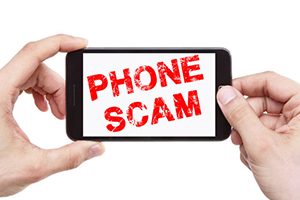 Image of a person holding a phone that says Phone Scam