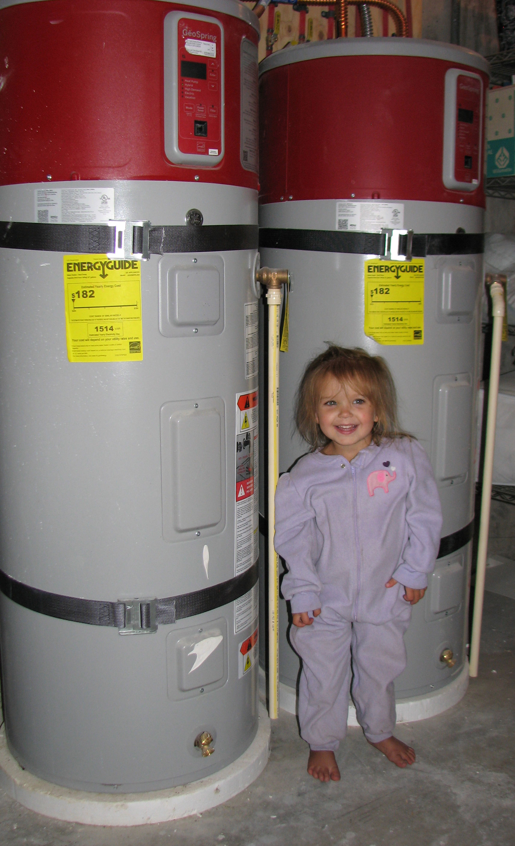 Little girl poses with her home's two heat pump water heaters