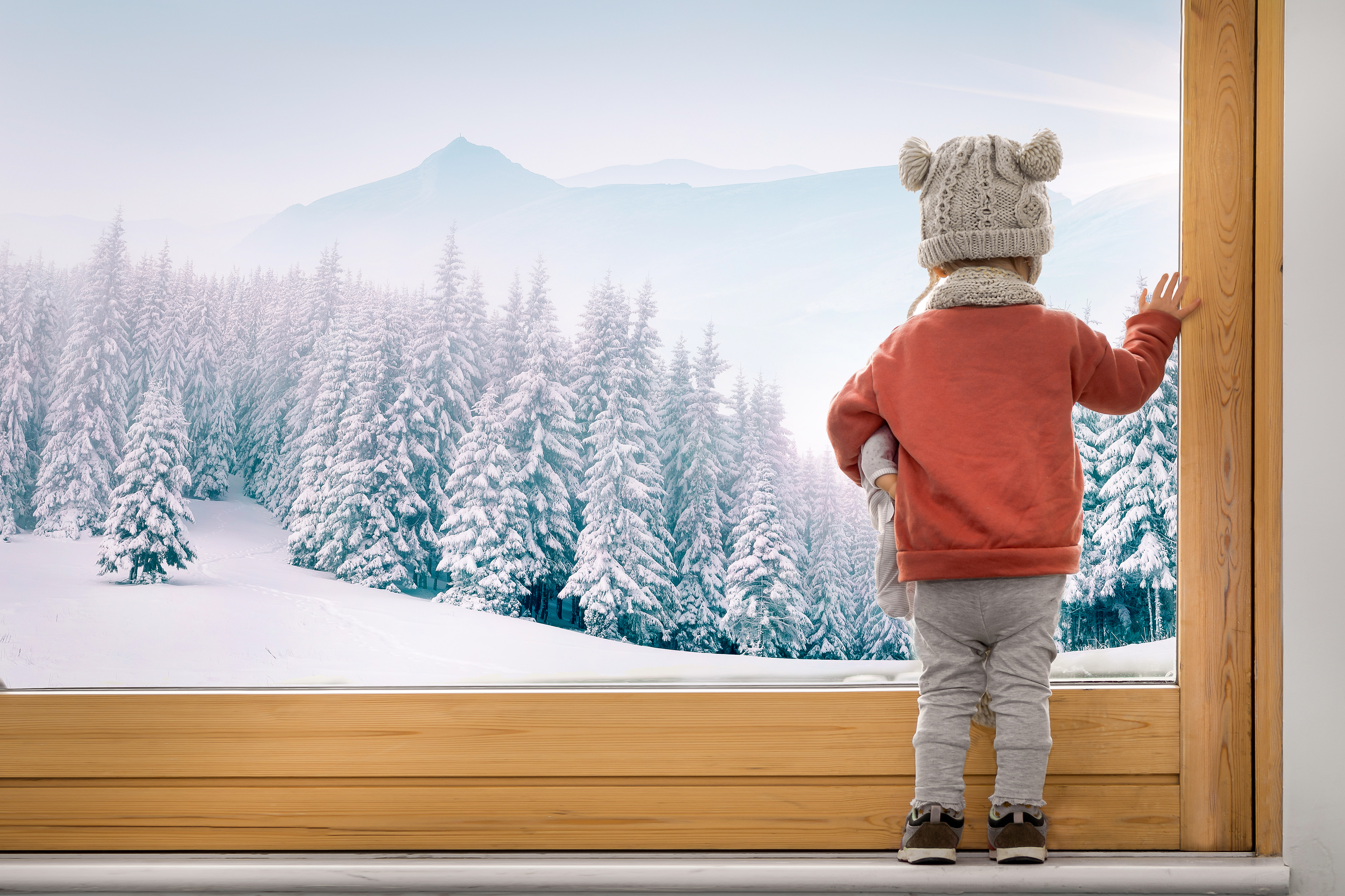 Toddler looks out window on to snowy winter scene
