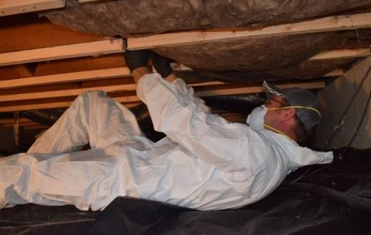 Low-Income Weatherization Program - person installing insulation in crawlspace of house