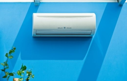 Ductless heat pump head on a bright blue wall