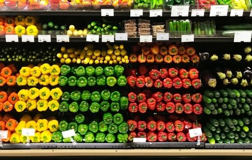 Refrigerated display stocked with vegetables in grocery store