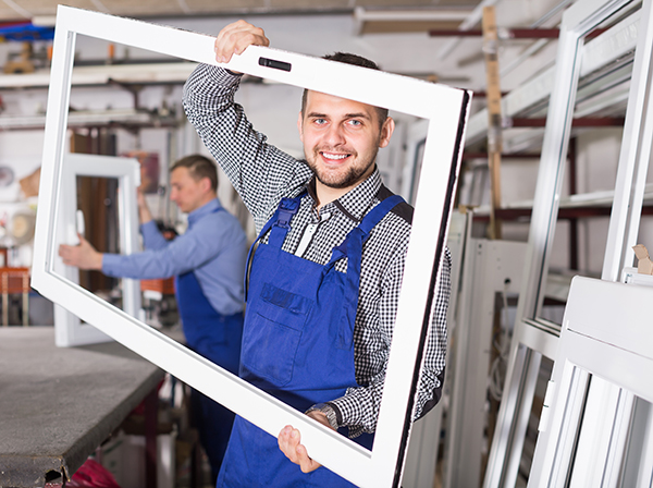 Photo of window installer holding window looking through glass